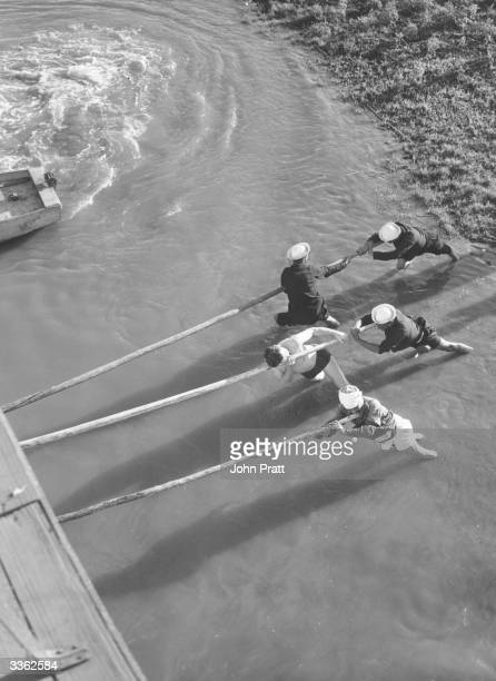 A ship's crew attempting to shift their boat off a sandbank whilst travelling along the Nile Egypt
