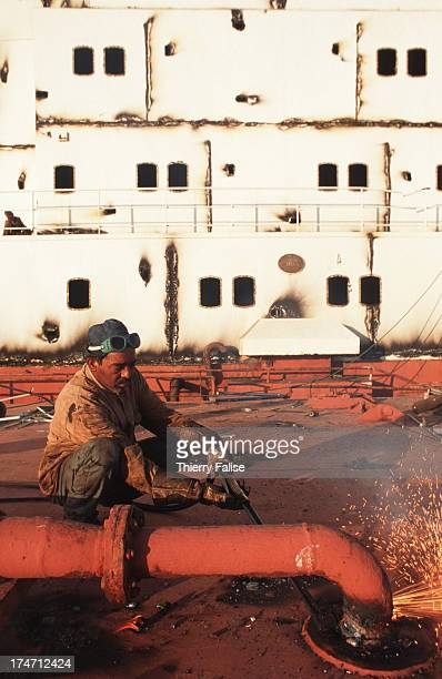 Ships demolition yard workers in Gadani cutting metal pieces
