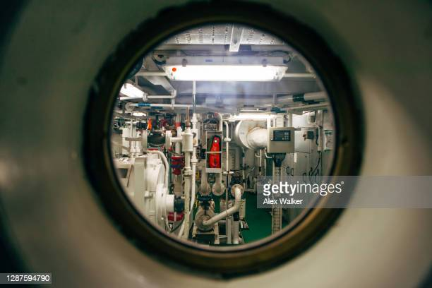 ships engine room through porthole - industry stock pictures, royalty-free photos & images
