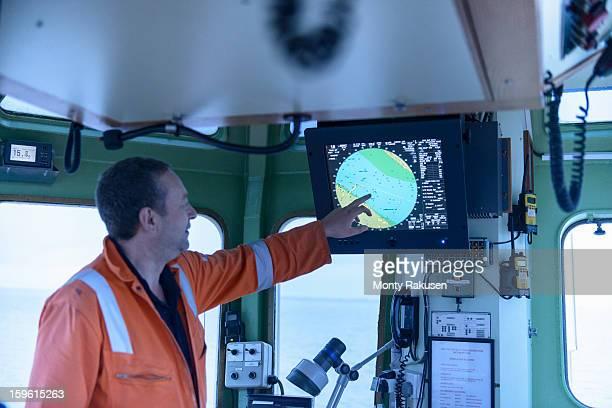 Ships mate pointing at digital chart on monitor on tug