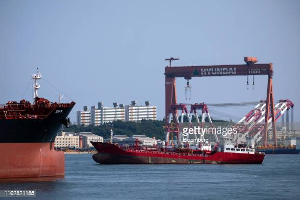 Ships sail in front of a gantry crane at a Hyundai Heavy Industries Co. Shipyard in Ulsan, South Korea, on Sunday, Aug. 4, 2019. Ulsan is known as...