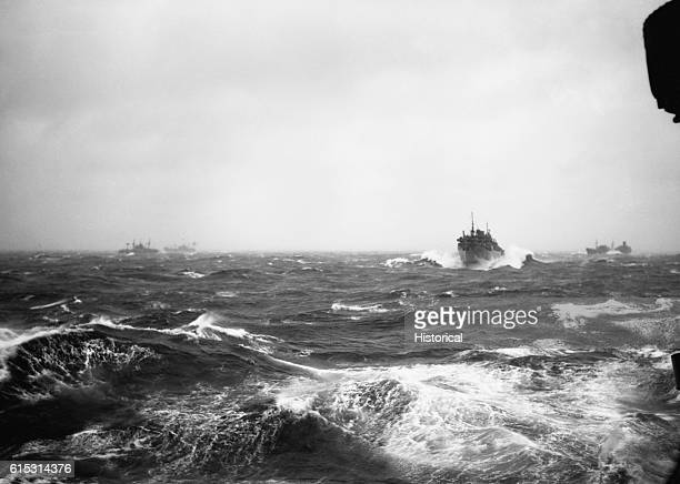 Ships travelling in convoy in the North Atlantic dot the horizon through rough seas. World War II.