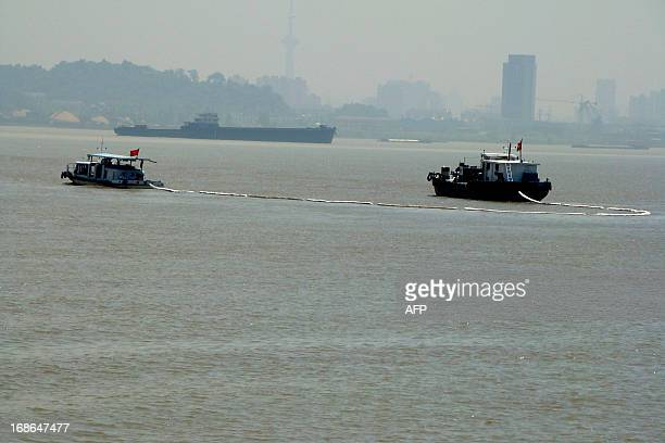 Ships work on the water after a vessel hit a bridge pier on the Yangtze River and sunk and leaked some petrol on May 13 2013 in Nanjing east China's...