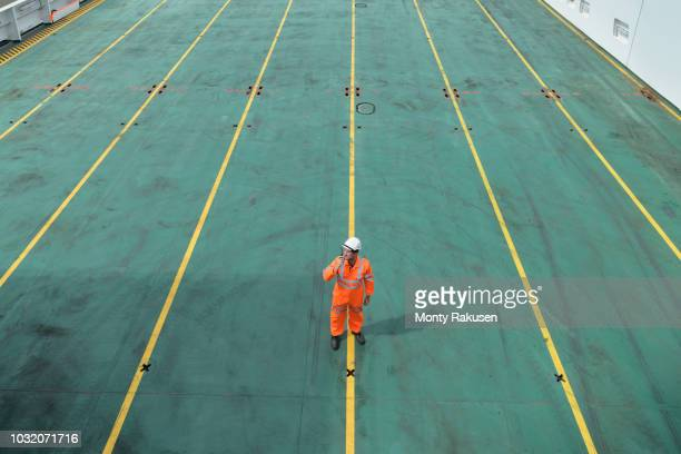 ship's worker using walkie talkie on deck of ship in port - diminishing perspective stock pictures, royalty-free photos & images
