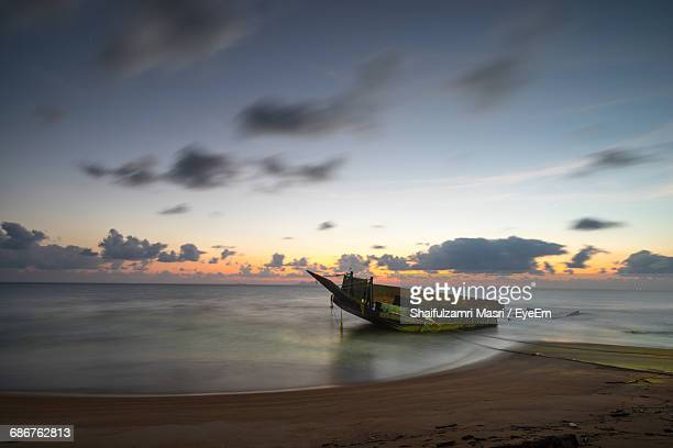 shipwreck at beach against sky during sunset - shaifulzamri eyeem stock pictures, royalty-free photos & images