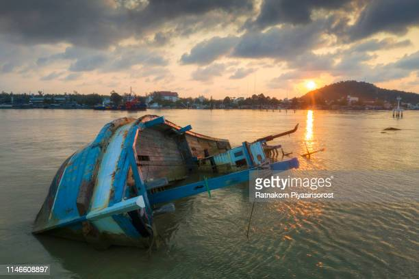 shipwreck or wrecked fishing ship in the sunrise scene ,thailand - sinking stock pictures, royalty-free photos & images