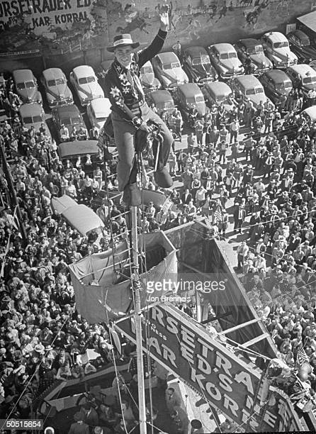 Shipwreck' Van Nolen sitting on a flagpole with crowd below