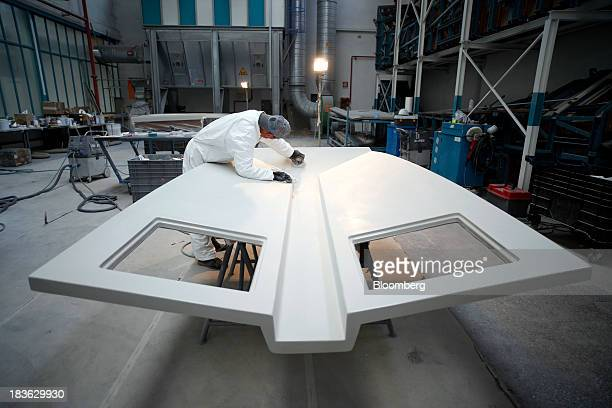 A shipwright uses a sander as he works on a molded fiberglass panel for a luxury yacht manufactured by Ferretti Group at the company's shipyard in...
