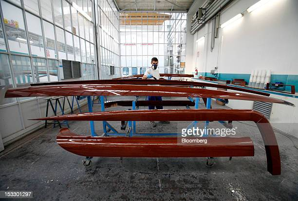 A shipwright varnishes wooden panels inside Riva's luxury boat building shipyard in Sarnico Italy on Tuesday Oct 2 2012 Ferretti Group whose Riva...