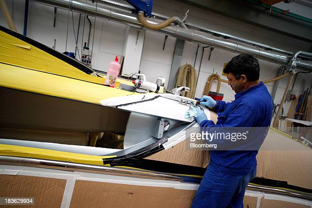 A shipwright works on a Riva Rivarama Super luxury yacht manufactured by Ferretti Group at the company's shipyard in Sarnico Italy on Monday Oct 7...