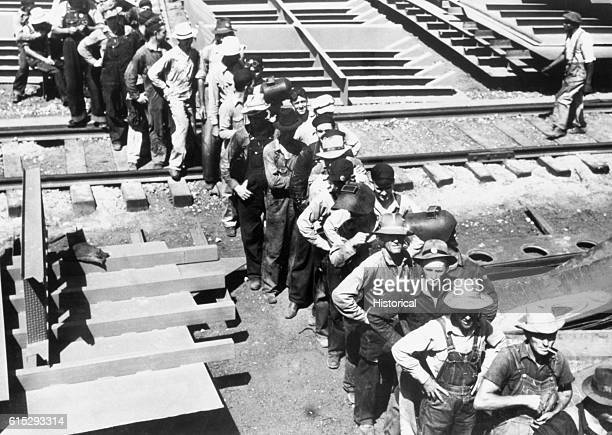 Shipwrights stand in a line to receive their payroll at the Ingalls shipbuilding company in Decatur Alabama July 1942