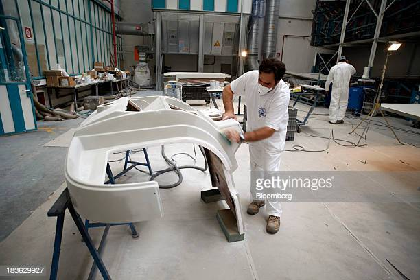 Shipwrights work on molded fiberglass panels for luxury yachts manufactured by Ferretti Group at the company's shipyard in Sarnico Italy on Monday...