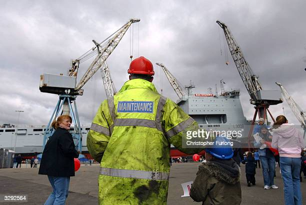 A shipyard worker takes his son to see Mounts Bay a newly constructed landing craft for the Royal Fleet Auxiliary slide down the slipway into the...