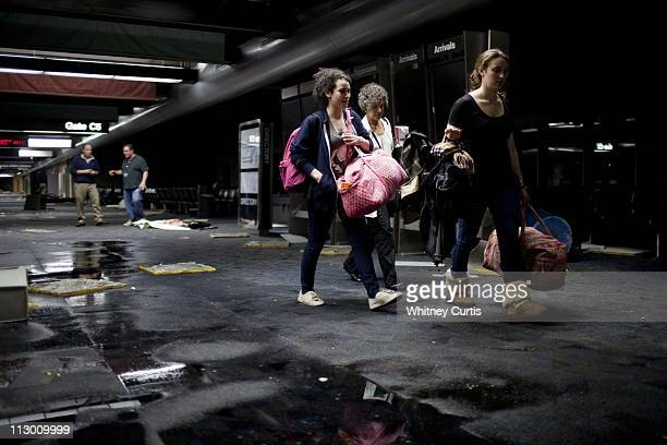 Shira Moskowitz Liza Karsten and her daughter Kate Nienaltow of New York City pick up their carryon items inside Concourse C after an apparent...