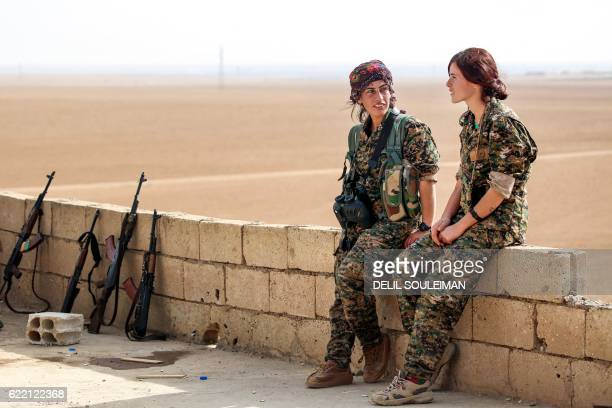 TOPSHOT Shirin and Kazîwar members of the Kurdish female Women's Protection Units engage in conversation next to Kalashnikov assault rifles on a...