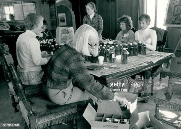 Shirley Baker loads vinegar into cases while others prepare the bottles Rear left to right Elaine Jackson Nancy Reece Sue Katherine Whitcomb Loli...