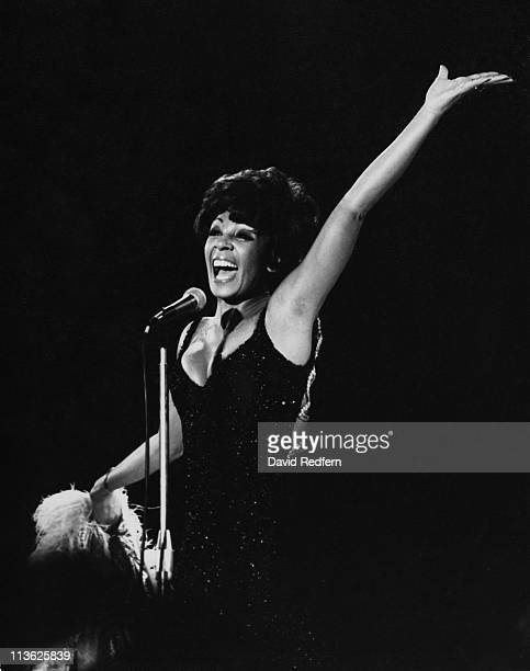 Shirley Bassey British singer singing into a microphone while raising her arm in a triumphant gesture during a live concert performance in...