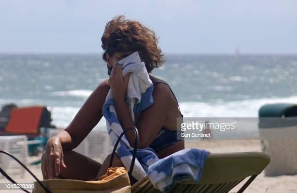 Shirley Bonin of Quebec shields her face from the wind in Deerfield Beach Fla Thursday Oct 4 2018 Officials have confirmed that red tide has appeared...