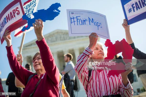 Shirley Connuck right of Falls Church Va holds up a sign representing a district in Texas as the Supreme Court hears a case on possible partisan...