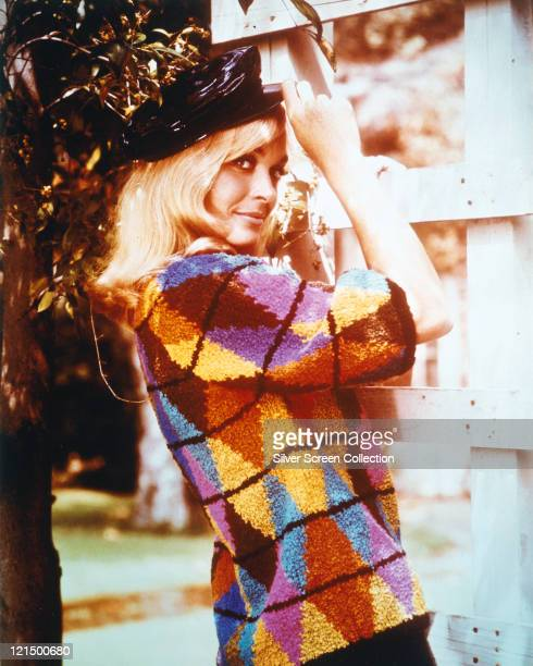 Shirley Eaton British actress wearing a multicoloured patterned jumper while posing with a peaked black cap on her head circa 1965
