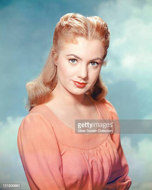 Shirley Jones US actress and singer wearing a salmon pink roundneck top in a studio portrait against a background of blue sky and clouds circa 1955