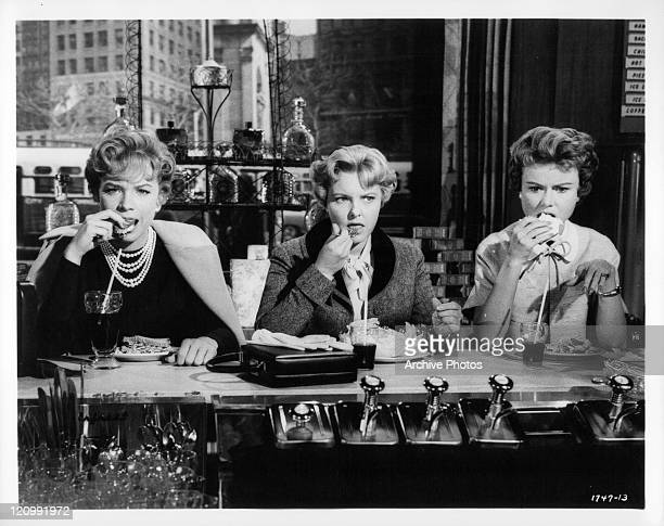Shirley MacLaine Elizabeth Fraser and Dody Heath eat at bar in a scene from the film 'Ask Any Girl' 1959