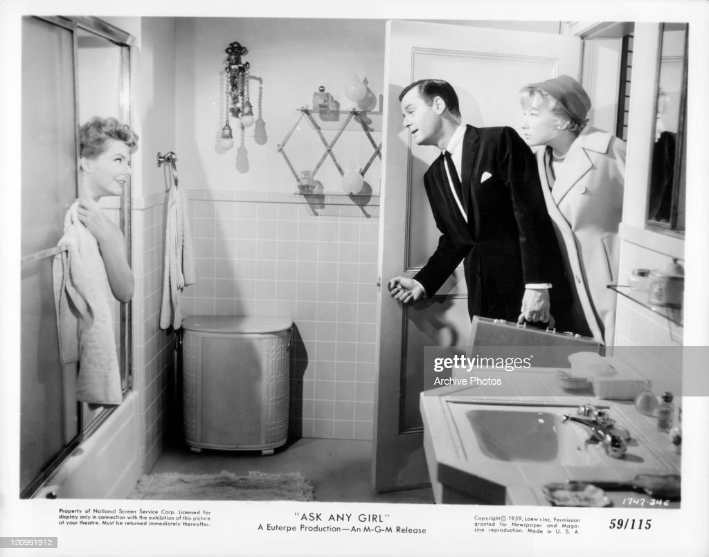 Shirley MacLaine looks into bathroom with man at woman in the shower in a scene from the film 'Ask Any Girl', 1959.