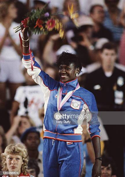 Shirley Strong of Great Britain looks on as Benita FitzgeraldBrown of the United States celebrates winning the gold medal in the Women's 100 metres...