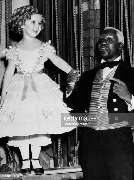 Shirley Temple avec le danseur Bill Robinson à une fête à Hollywood Californie EtatsUnis le 13 décembre 1935
