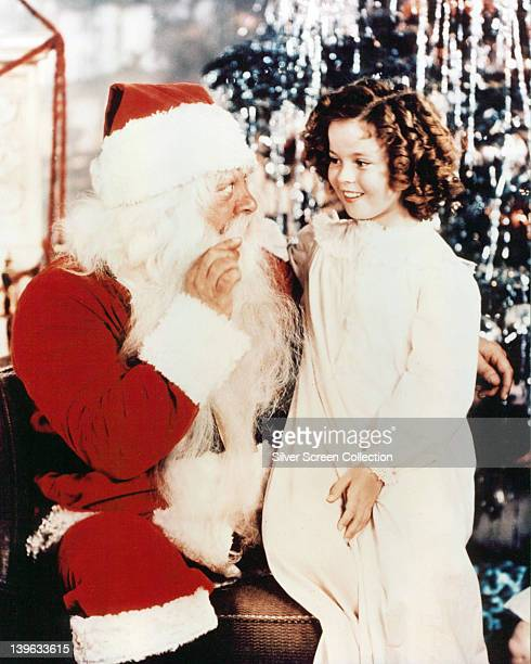 Shirley Temple US child actress wearing a white nightgown and sitting beside a man dressed as Father Christmas circa 1935