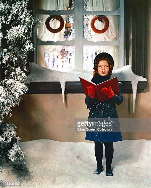 Shirley Temple US child star poses in winter clothes holding an open book in front of window with icicles falling from the window ledge with...