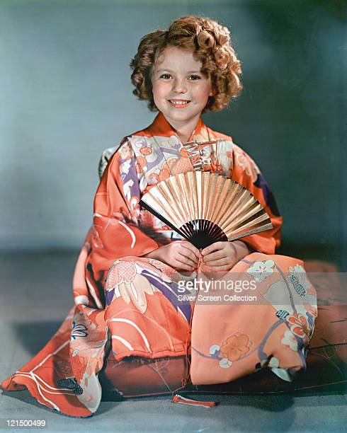 Shirley Temple US child star wearing a peachcoloured floral kimono holding a fan in a studio portrait circa 1940