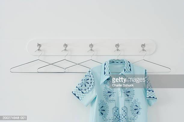 Shirt hanging amongst empty hangers on row of hooks