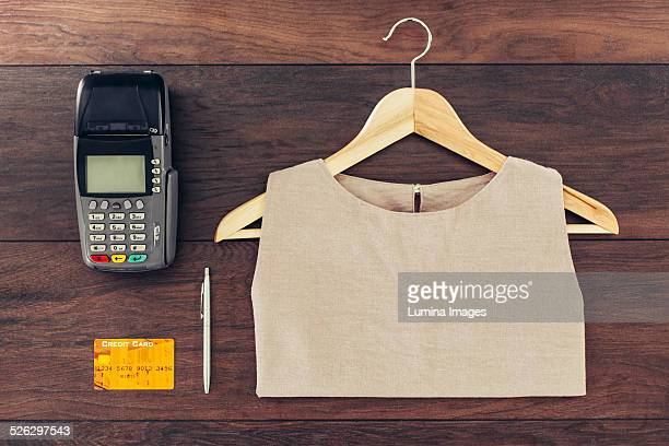 Shirt on hanger, credit card and machine on store counter