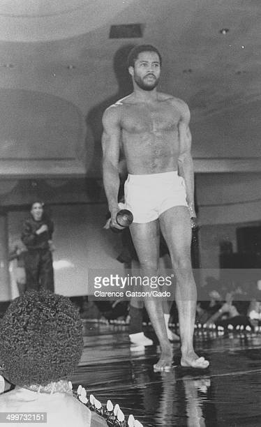 Shirtless AfricanAmerican male model with weights posing on stage during a fashion show San Francisco California 1980