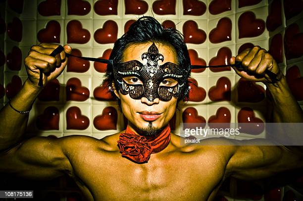 shirtless asian man ties on mask against heart background
