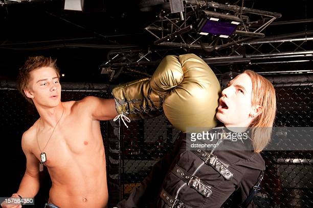 shirtless boxer punching punk with oversize boxing glove - boxing golden gloves stock photos and pictures