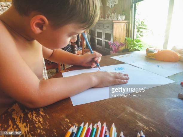 Shirtless Boy Drawing On Paper At Home
