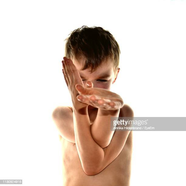Shirtless Boy Performing Martial Arts Against White Background
