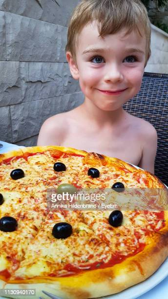 Shirtless Boy Sitting By Pizza