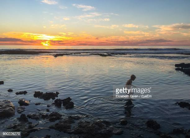 Shirtless Boy Wading In Sea Against Sky During Sunset