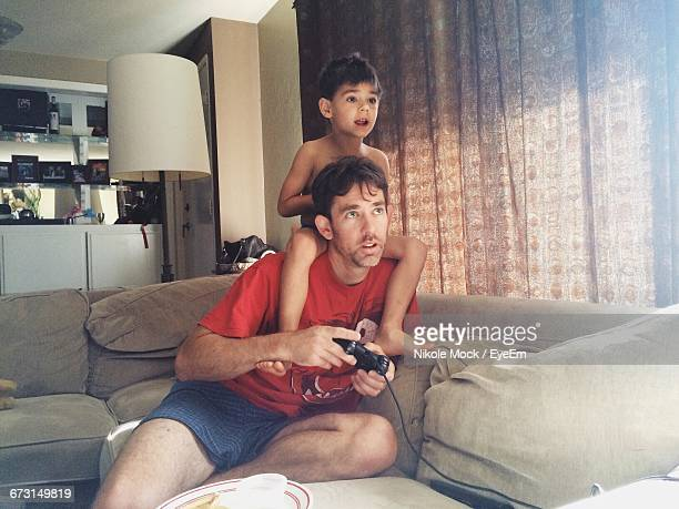 Shirtless Boy With Father Playing Video Game At Home