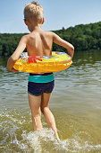 shirtless boy with inflatable ring wading