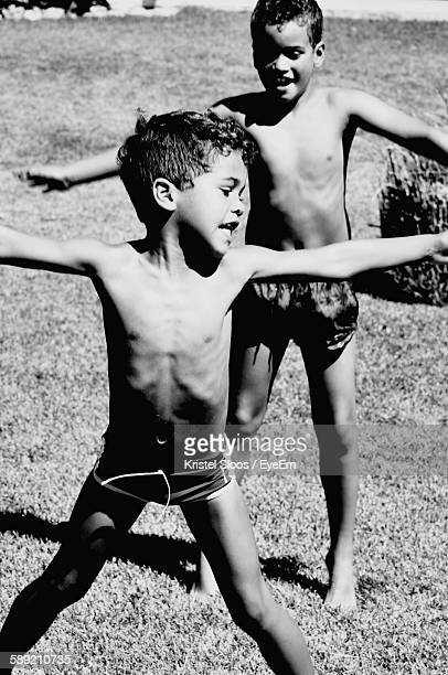 Shirtless Boys Standing With Arms Outstretched On Field