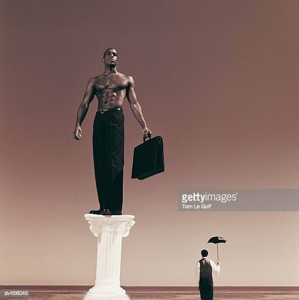 Shirtless businessman on pedestal with briefcase