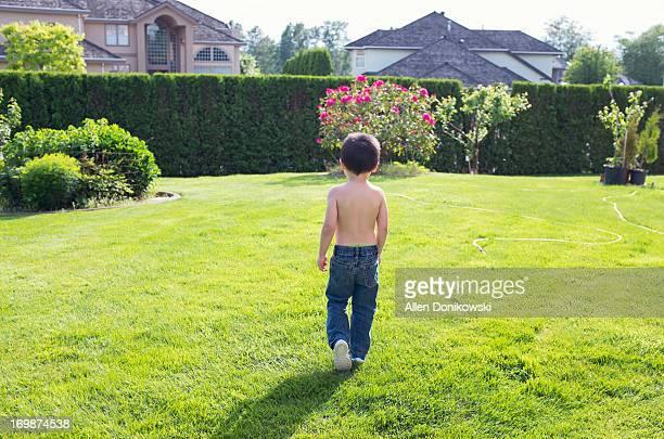 shirtless child walking in grass yard during day