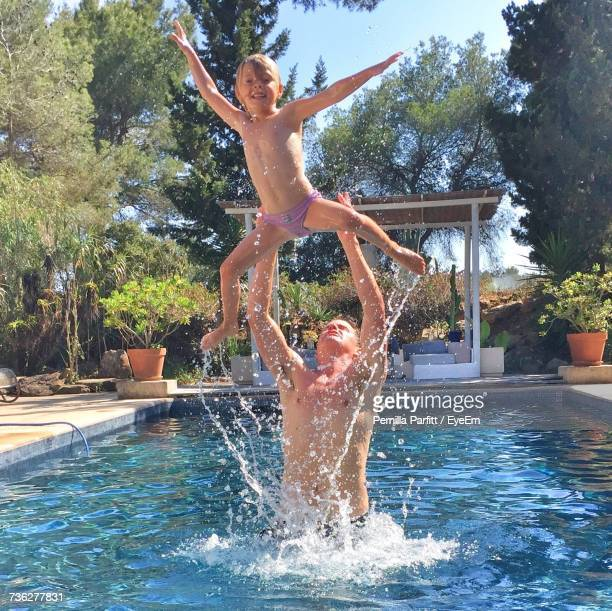Shirtless Father Throwing Son While Standing In Swimming Pool
