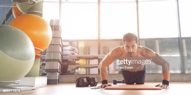 Shirtless fitness instructor posing in health club with dumbbell