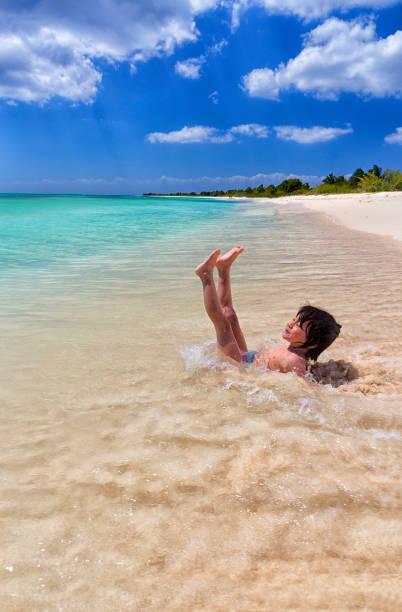Shirtless girl enjoying on sea shore at beach during summer vacation, Punta Sur, Cozumel, Mexico