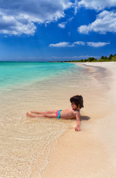Shirtless girl playing on sea shore at beach during summer vacation, Punta Sur, Cozumel, Mexico